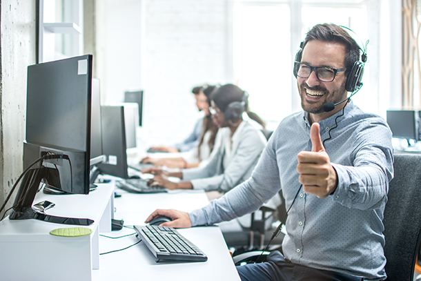 Cheerful male customer service operator showing thumbs up in office